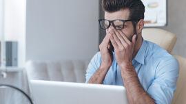 Mann müde erschöpft - Arbeiten Sie viel vor dem Bildschirm? Bei Computerarbeit sollten Sie Ihren Augen regelmäßige Verschnaufpausen gönnen. Schauen Sie zwischendurch öfter mal aus dem Fenster bzw. in die Ferne. Das tut unseren Augen gut. - © Shutterstock