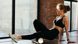 Frau trainiert ihre Faszien mit einer Faszienrolle - Mit regelmäßigem Faszientraining kann die allgemeine Beweglichkeit gesteigert werden.