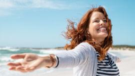 Frau genießt den Wind oder die Meeresbrise und streckt die Arme aus_shutterstock_1749759167 - Die Wechseljahre sind ein natürlicher Vorgang im Leben jeder Frau.