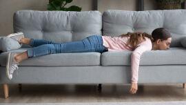 Frau liegt erschöpft auf dem Sofa_Müde_shutterstock_1390236809 - Gegen Erschöpfung kann man einiges unternehmen.